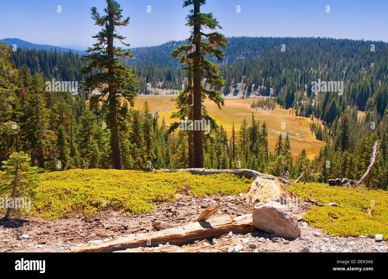 This image of Mount Lassen National Park shows beautiful hills and a valley adorned with greenery. - Stock Image