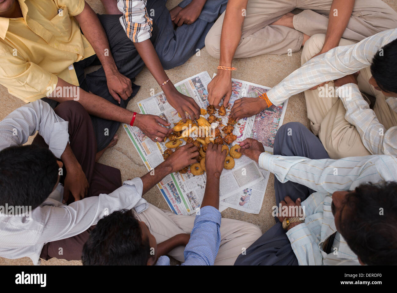 Indian mens right hands picking at Unhealthy deep fried indian street food / fast food. Andhra Pradesh, India - Stock Image
