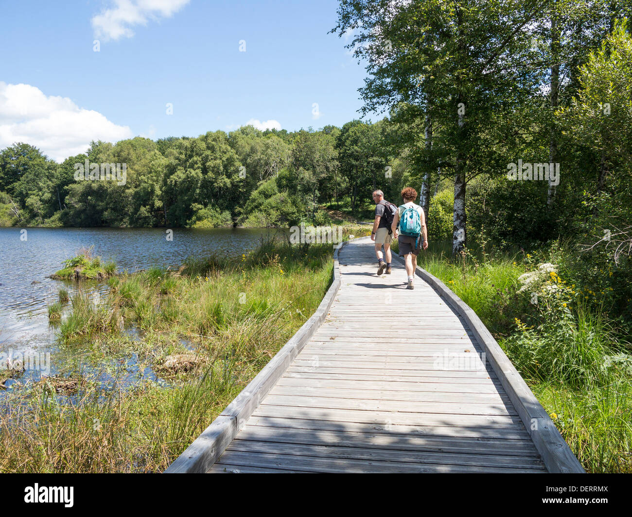Walkers with rucksacks on a boardwalk at the edge of Lake Vassiviere in the Plateau de Millevanche regional park, Limousin - Stock Image