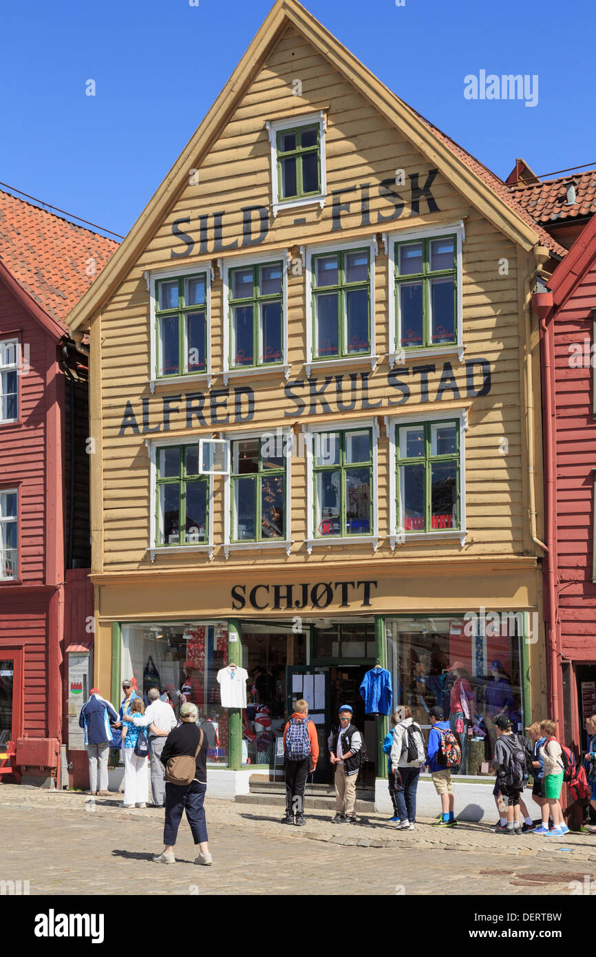 f5bb0f75 Tourists by a shop selling Norwegian gifts in old traditional wooden  building on Bryggen, Bergen, Hordaland, Norway, Scandinavia