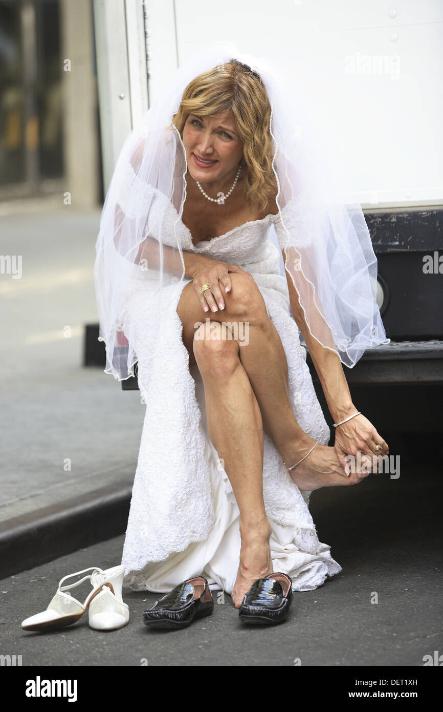 Bride sitting on bumper of truck massaging her aching feet - Stock Image