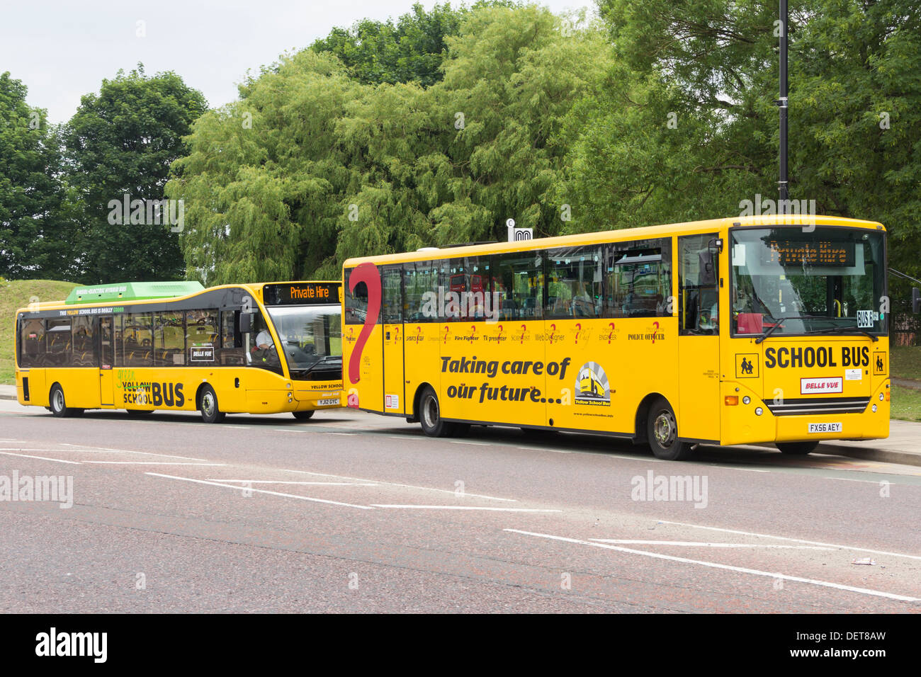 Two yellow school buses (UK variety) in Manchester. The rear bus is a Optare Versa Hybrid low diesel/electric emission vehicle. - Stock Image