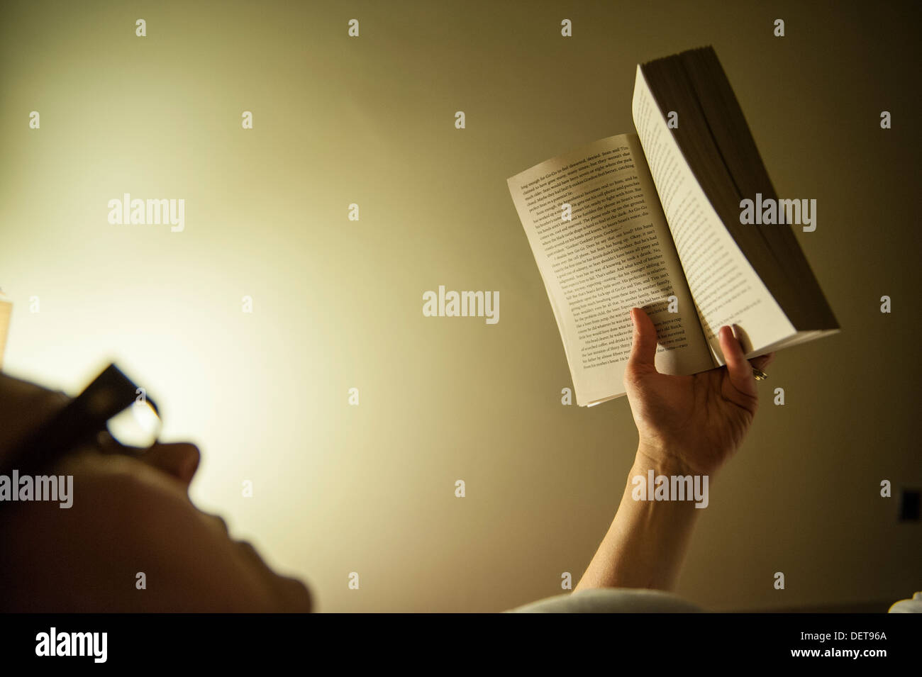 A woman reads in bed at night - Stock Image