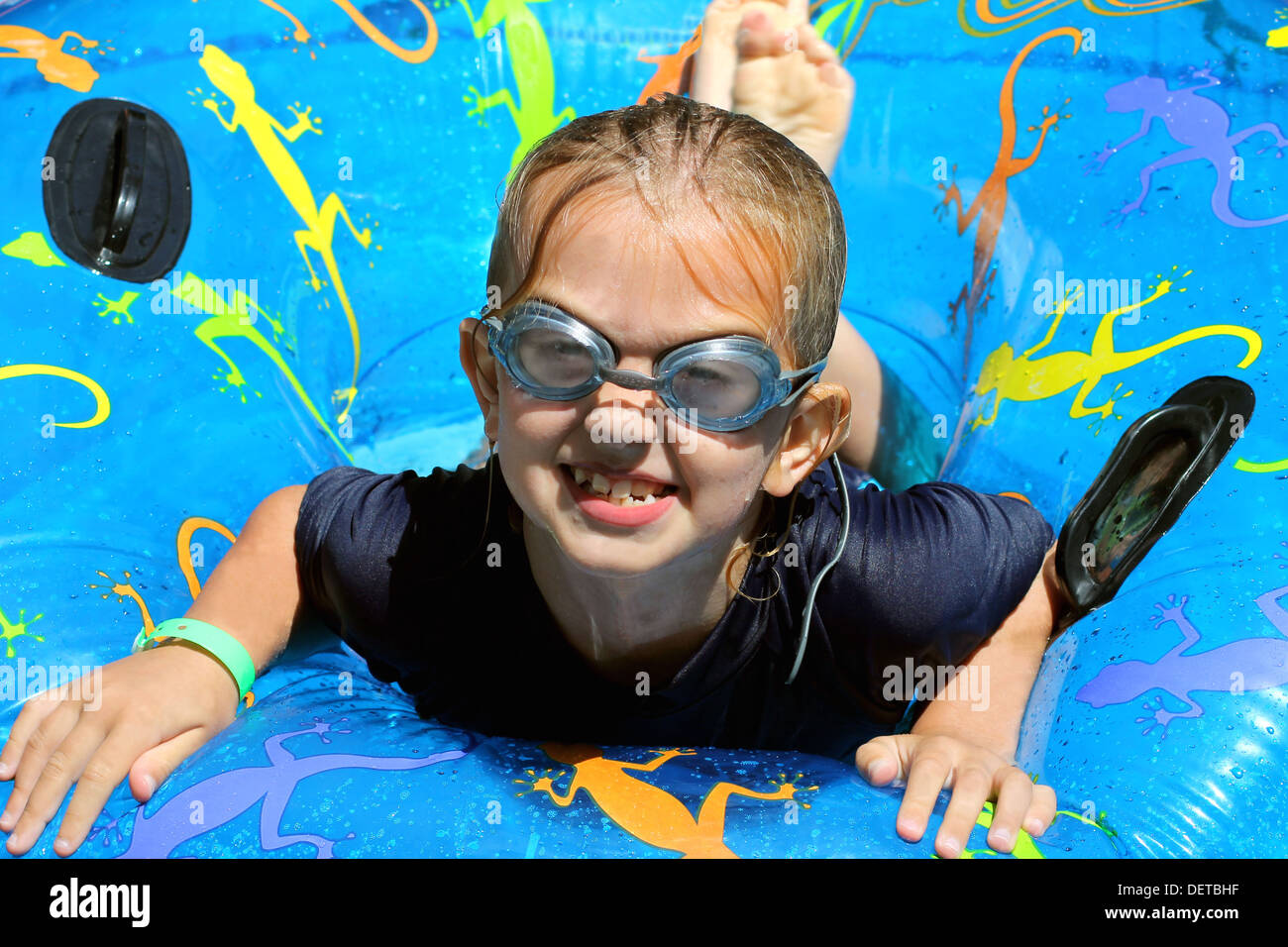Cute girl playing on inflatable in swimming pool. - Stock Image