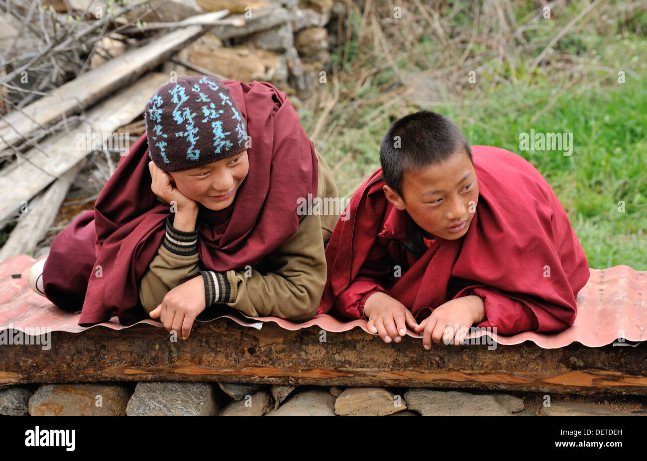 Young monks watching dancers at Domkhar Tsechu festival held in a monastery in the village of Domkhar, Bumthang, Bhutan - Stock Image