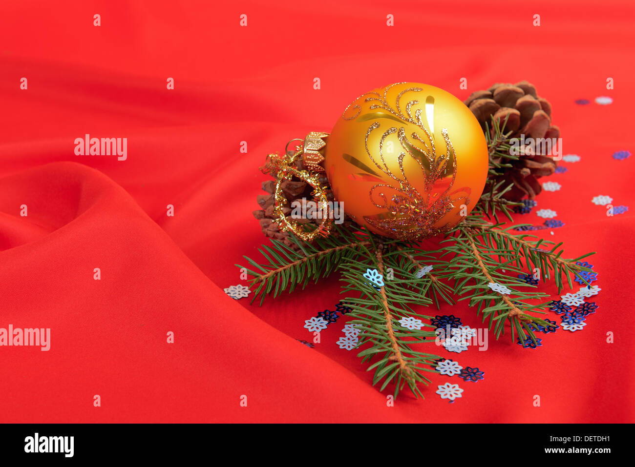 Christmas ball and pine tree branch decoration on red silk - Stock Image