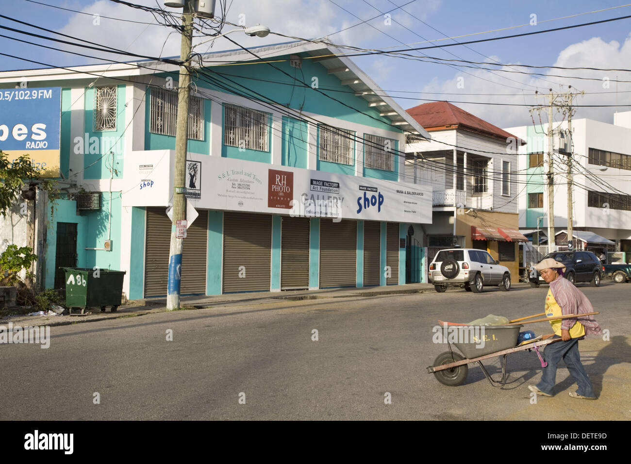 Lady street cleaner walks across road towards the Image Factory art foundation, Fort George District, Belize City, Belize - Stock Image