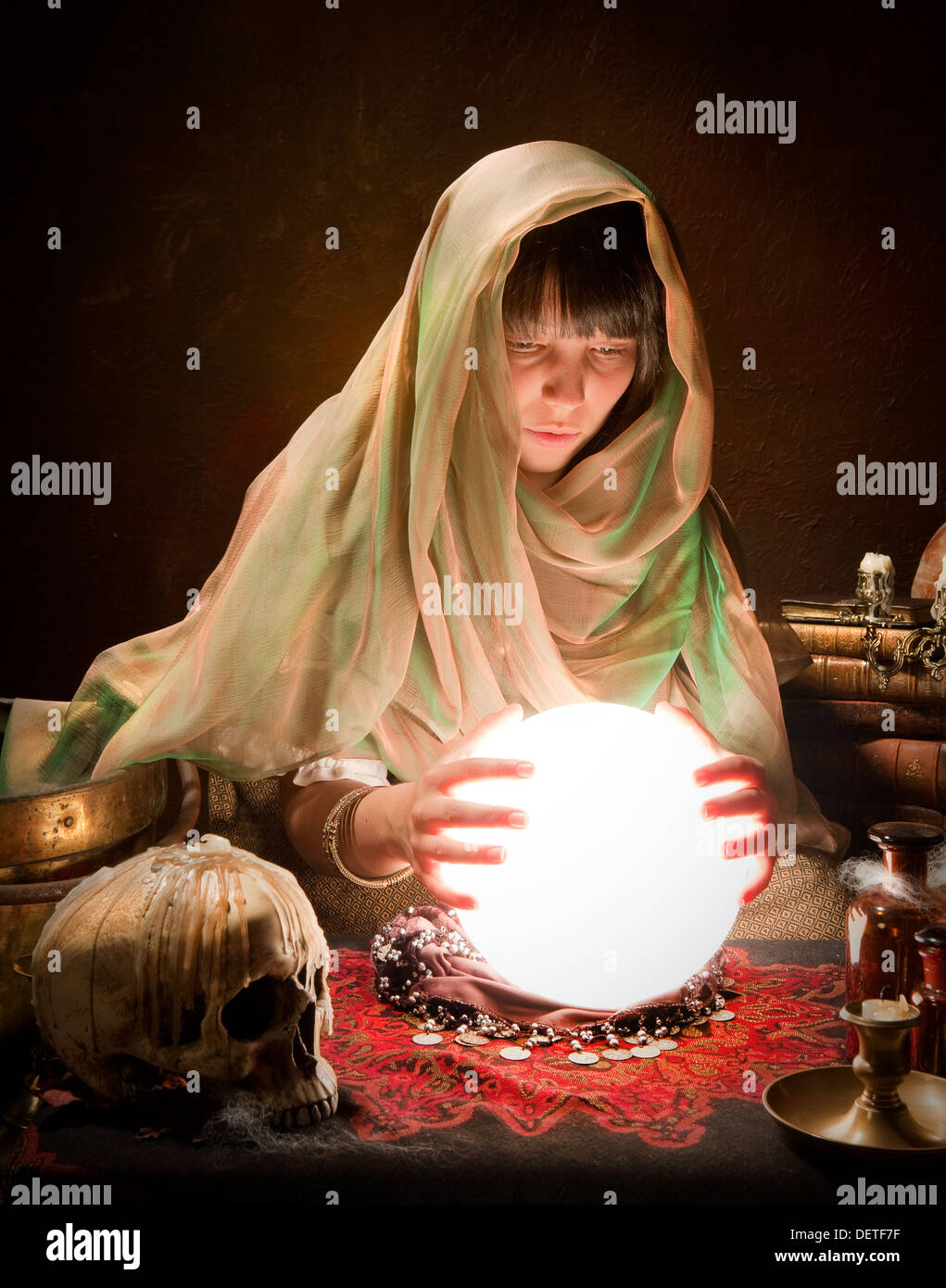 Young fortune-teller reading the future in a crystral ball - Stock Image
