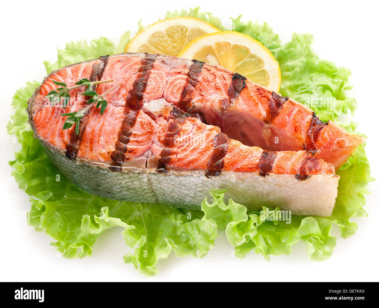Grilled salmon and with lemon slices overr lettuce leaves. Close up shot. - Stock Image