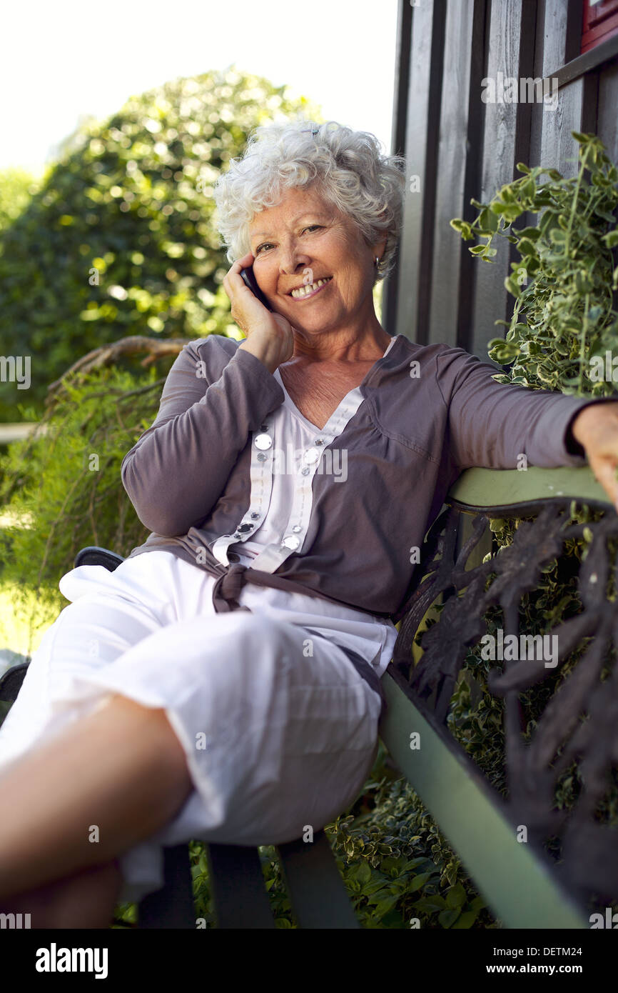 Happy senior woman sitting on a bench in backyard talking on mobile phone and smiling - Stock Image
