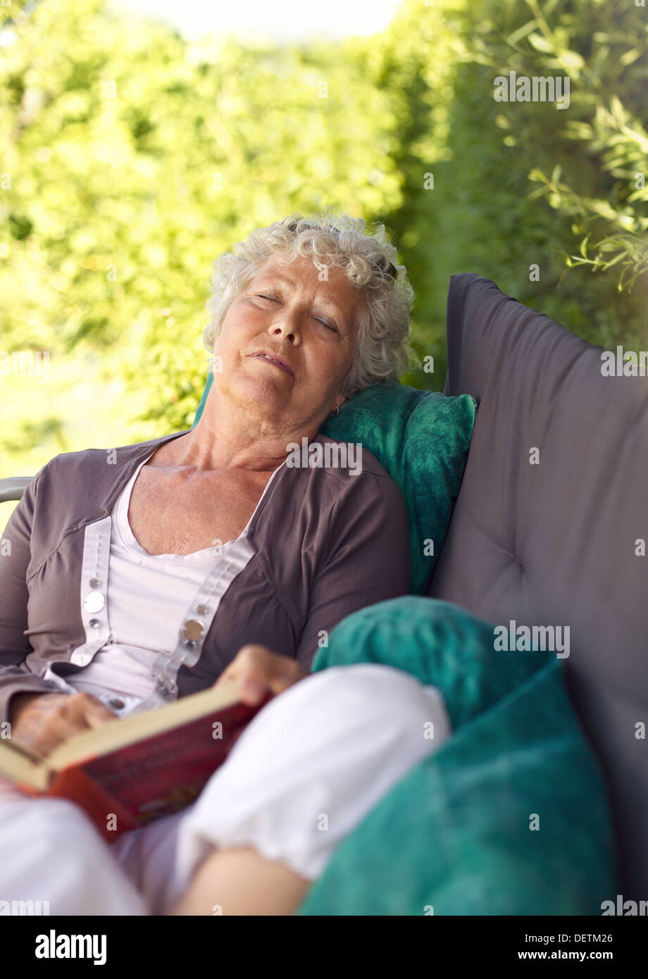 Senor woman sitting on lounge chair with a book and talking a nap. Senior lady sleeping in backyard with a novel - Stock Image