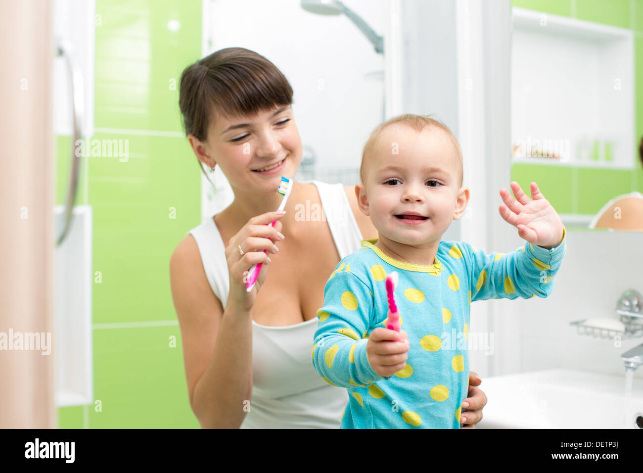 mother with baby brushing teeth - Stock Image