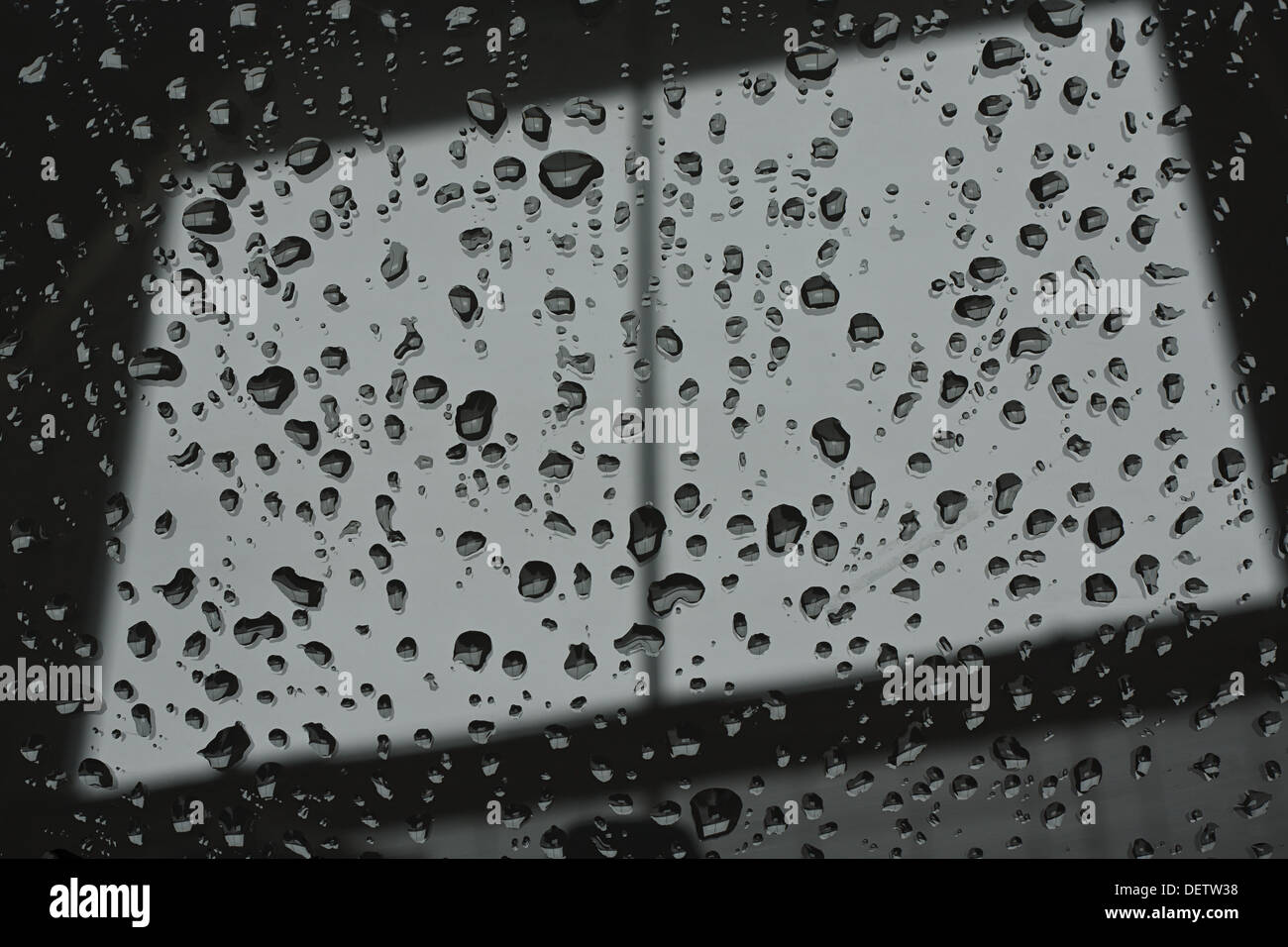 Abstract photograph of a window pane with raindrops on symbolising dull wintry weather - Stock Image