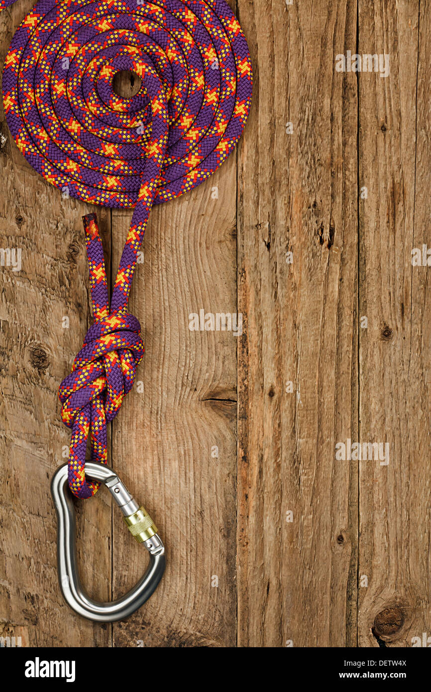 Rock climbing gear with rope and connector on rustic wooden background often used for belay or abseiling by mountaineers - Stock Image