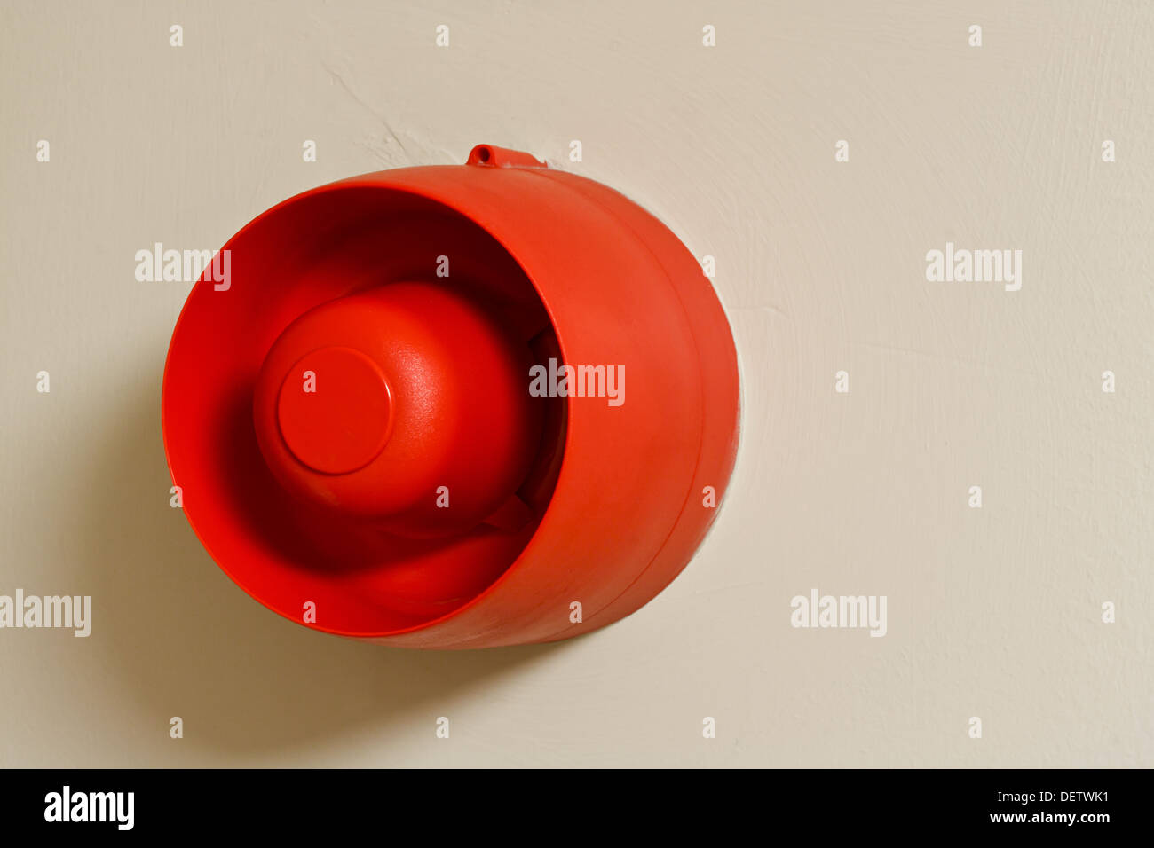 red wall mounted fire siren warning alarm used to alert people to danger in buildings - Stock Image