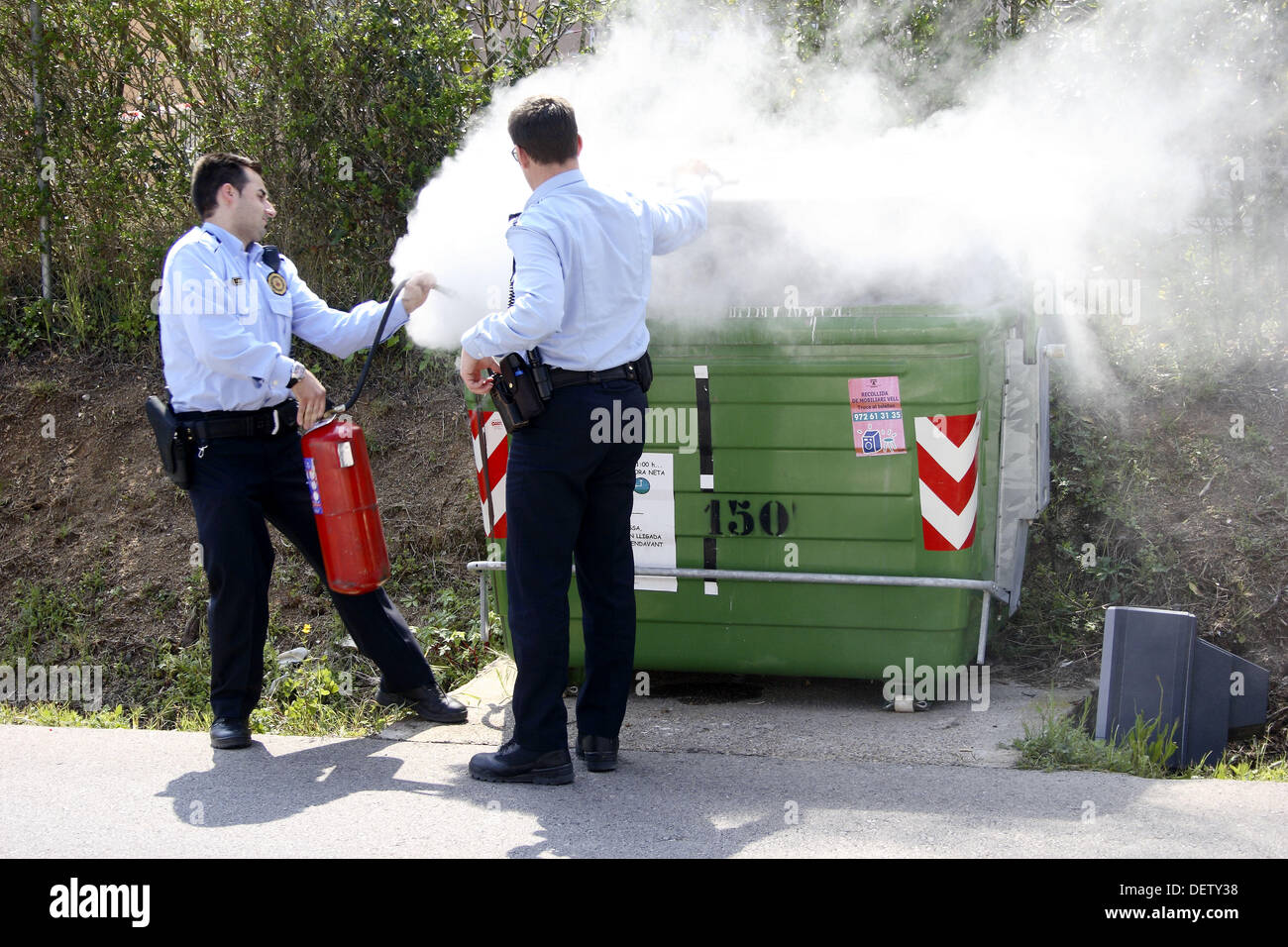 Local police fighting a fire in a rubbish container. - Stock Image