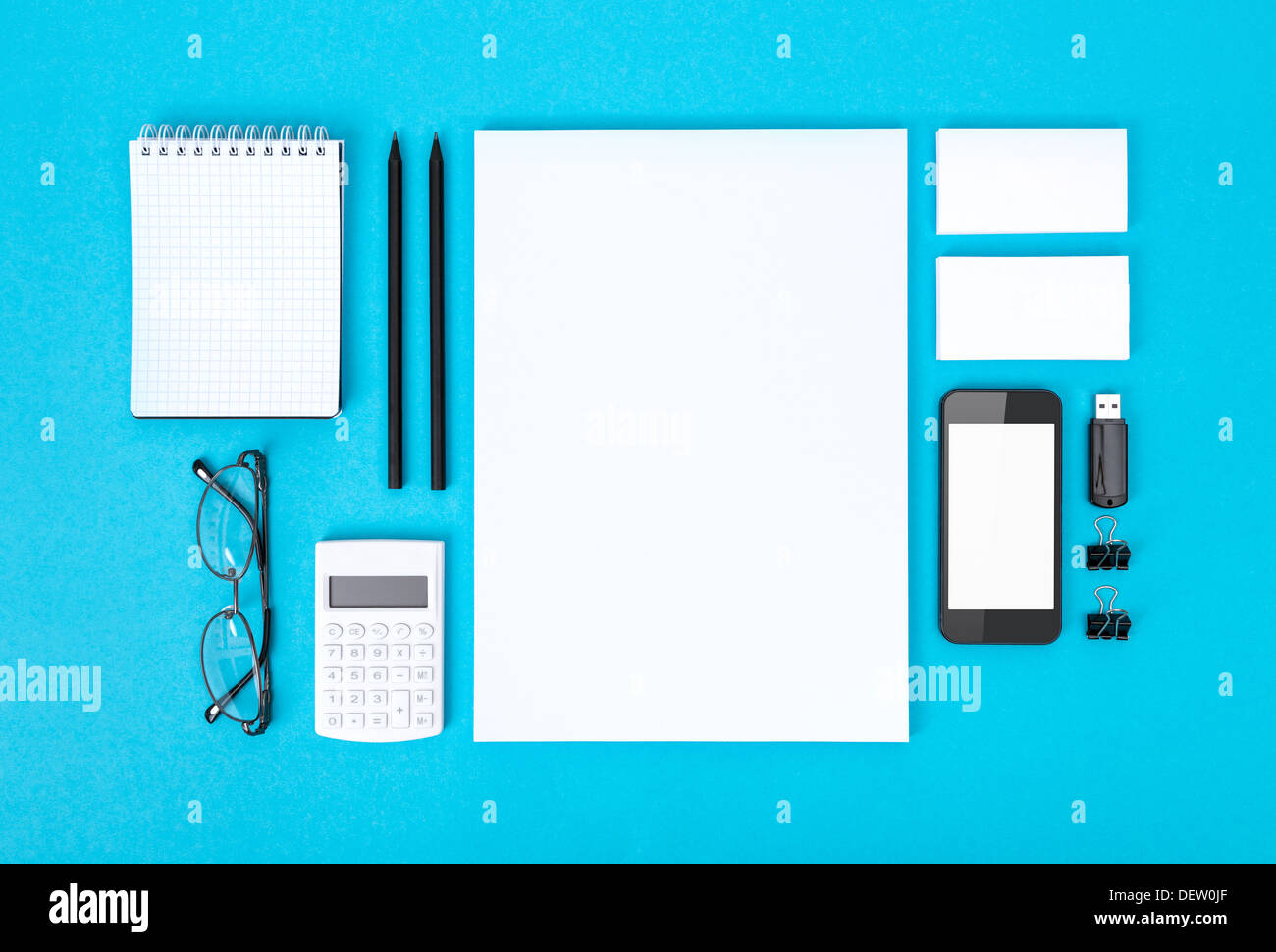 Set of variety blank office objects organized for company presentation or corporate identity. Isolated on blue paper - Stock Image