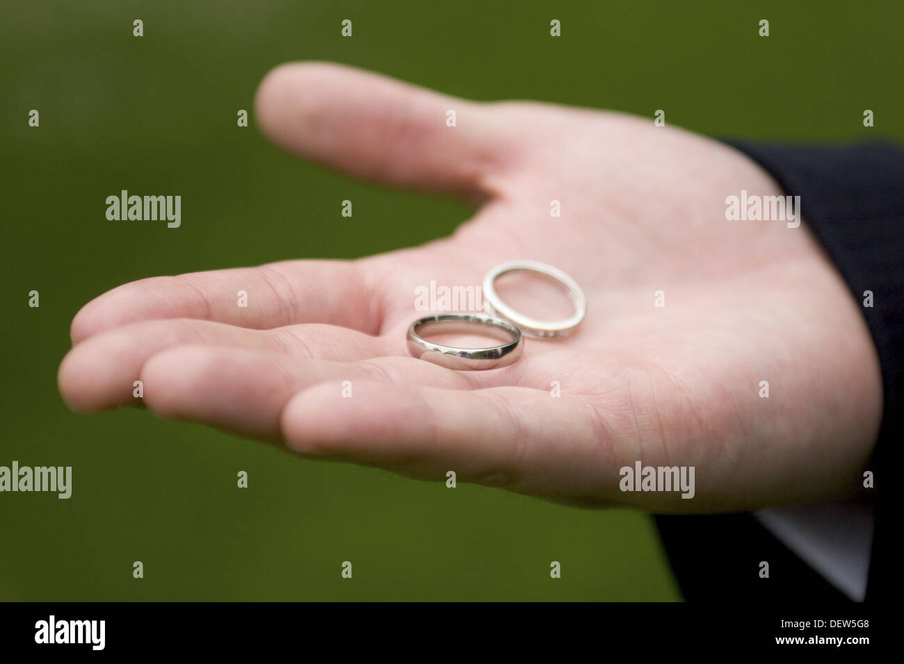 Two white gold wedding rings rest in a groom´s open hand against a ...