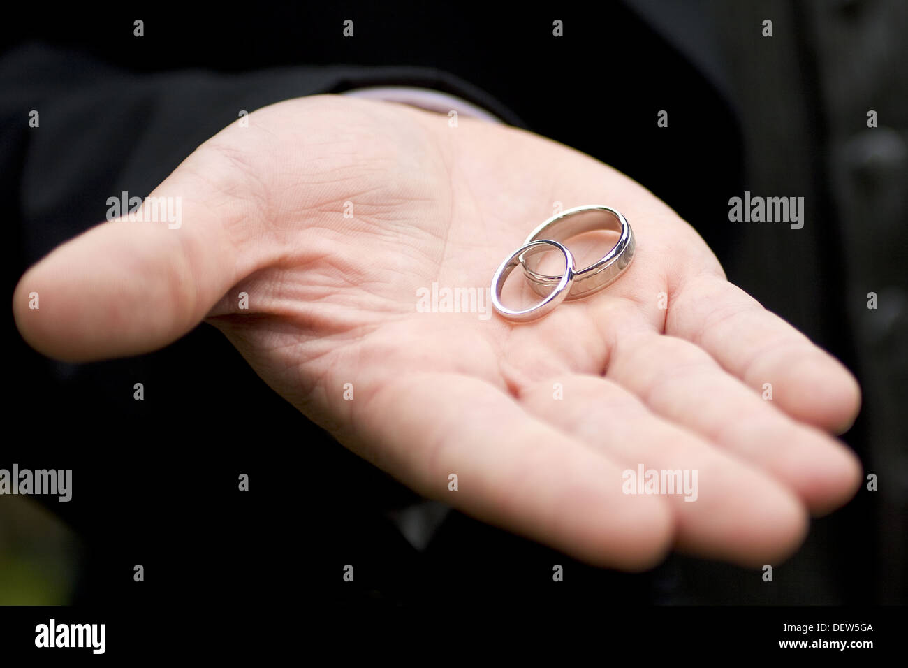Two white gold wedding rings rest in the open hand of the groom ...