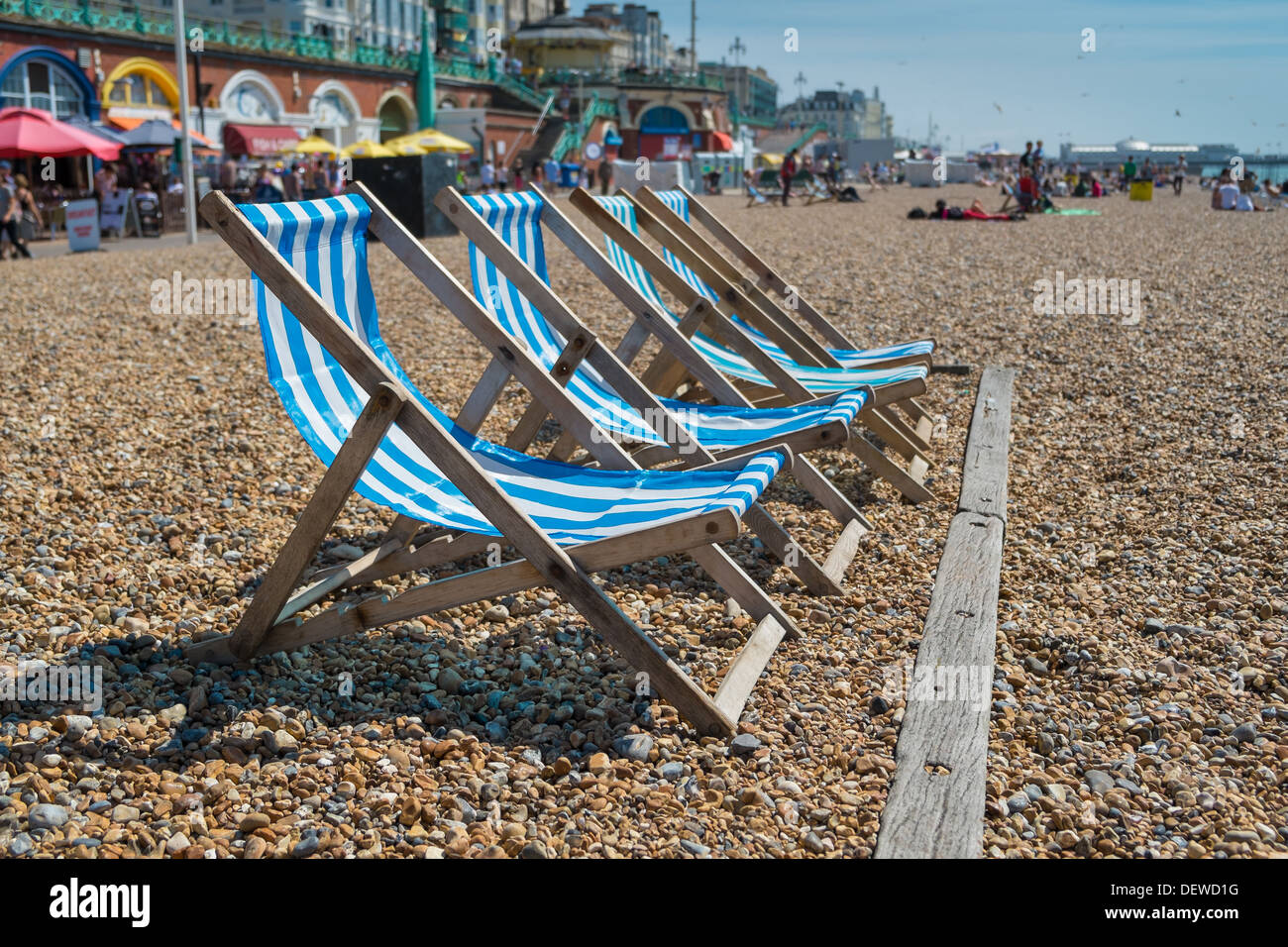 4 blue deck chairs on Brightons pebble beach - Stock Image