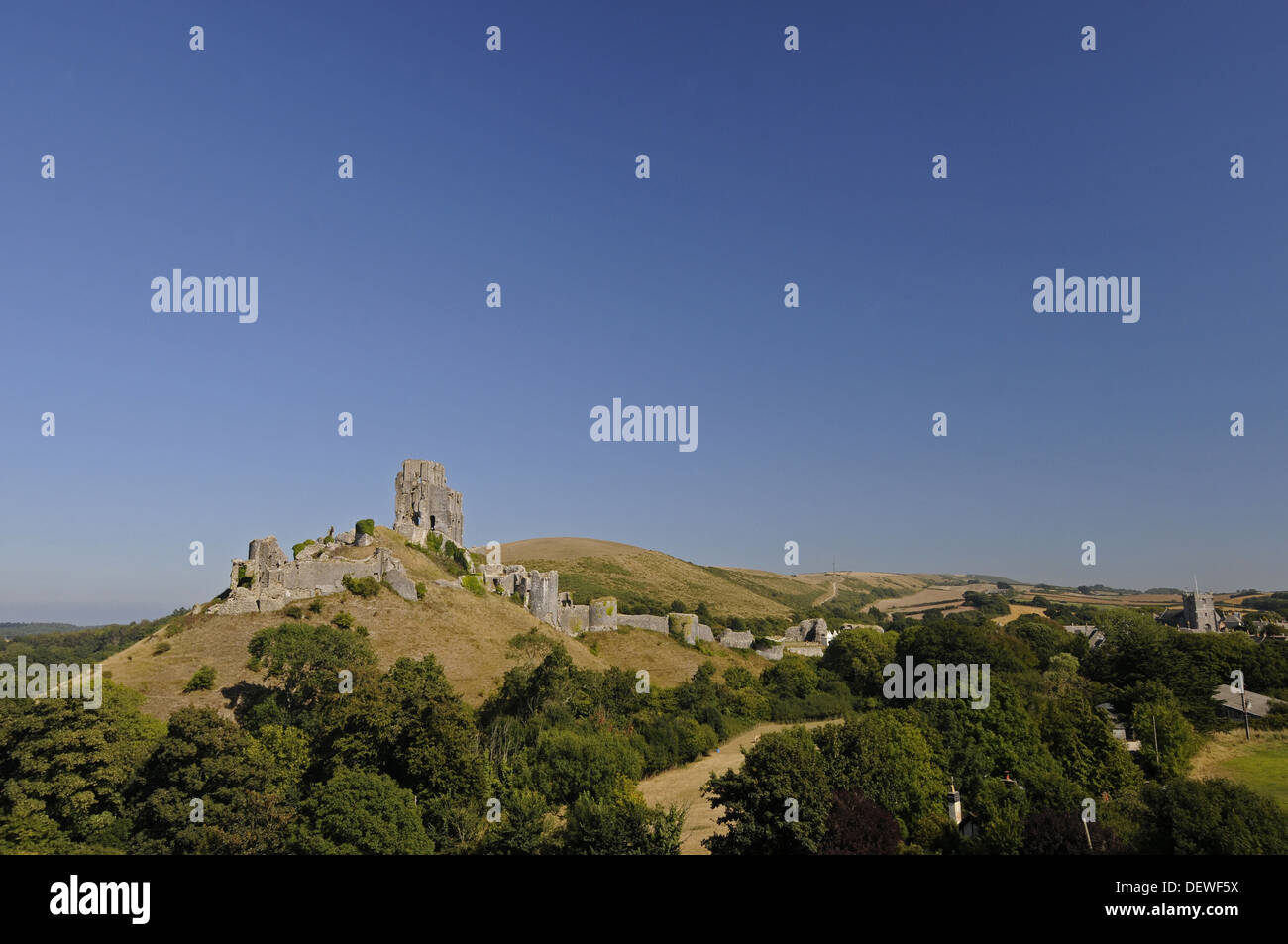 View over trees to ruins of Corfe Castle with village of Corfe in background , Isle of Purbeck Dorset England Stock Photo