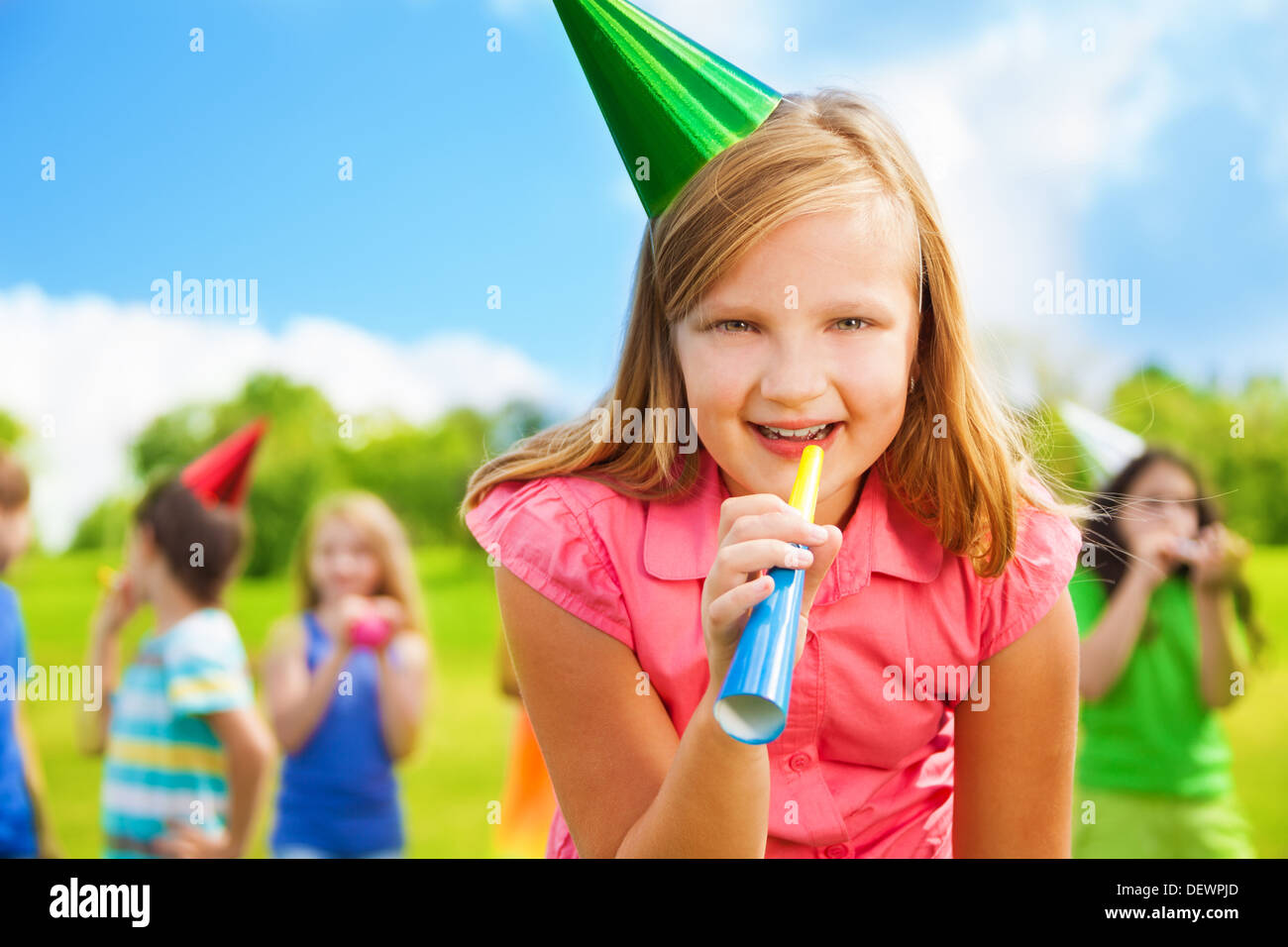 Portrait of happy girl with noisemaker whistle on a birthday party wearing cap with friends standing on background Stock Photo