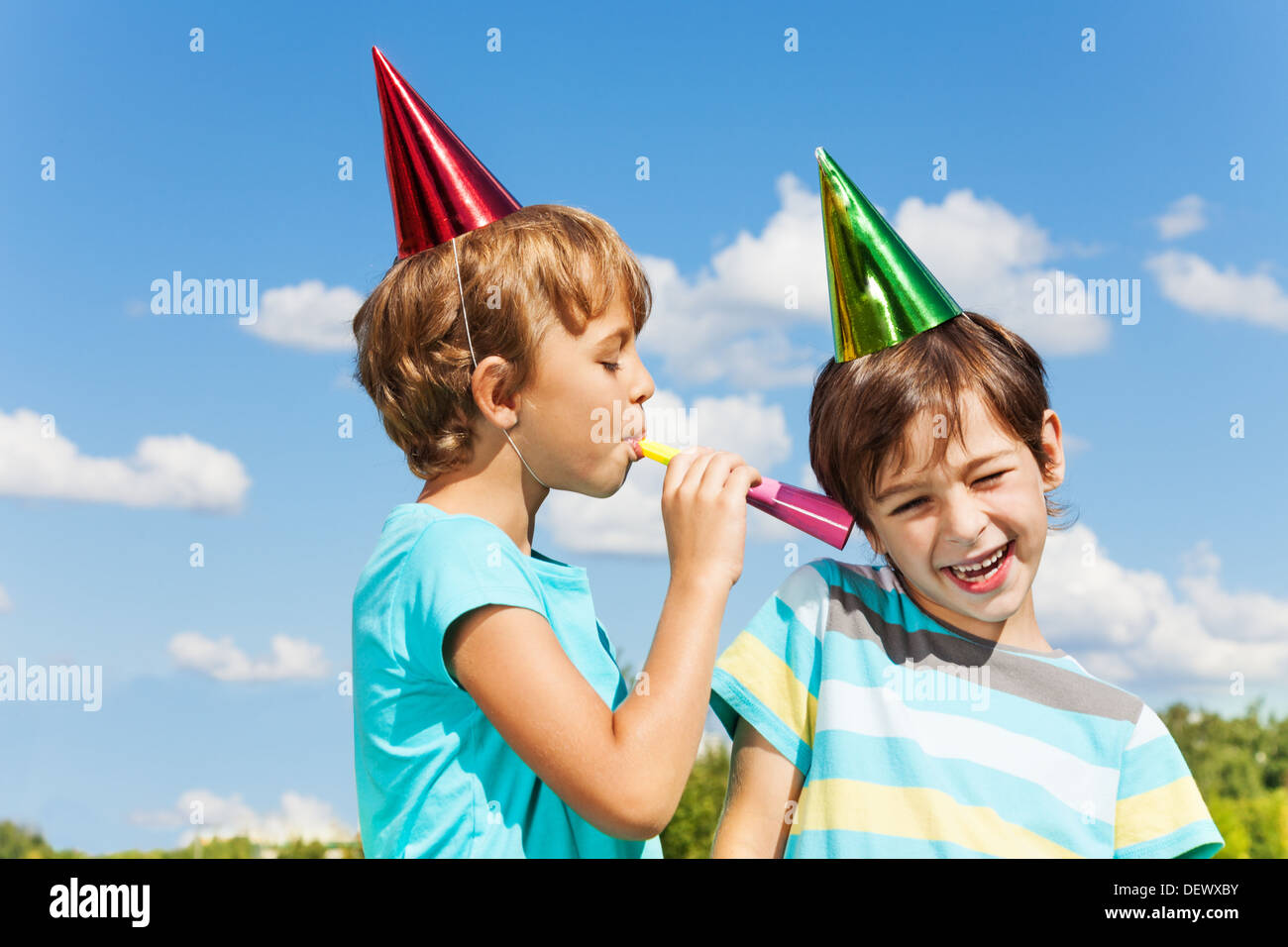 Two boys on birthday party having fun with blowing into noisemaker loudly  - Stock Image