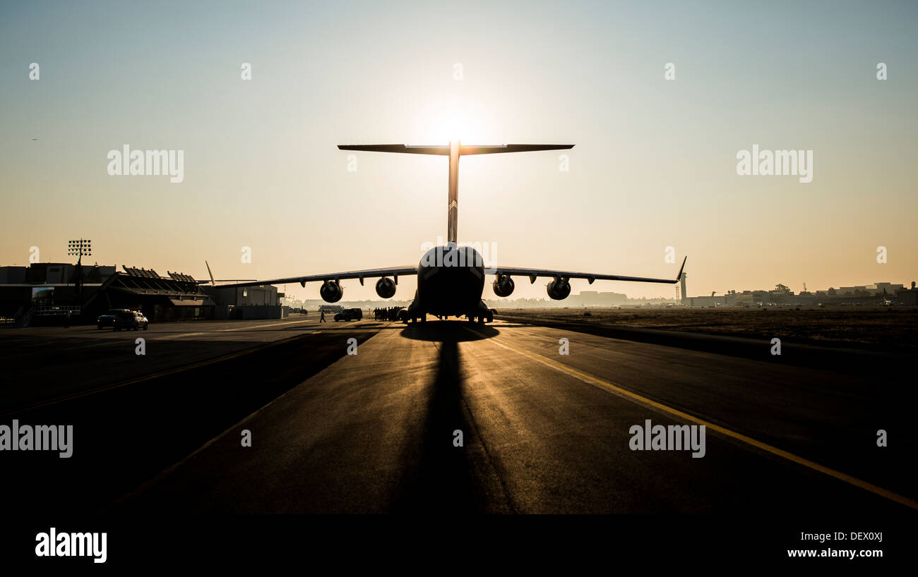 The sun rises above the final U.S. Air Force C-17 Globemaster III, P-223, as crew members arrive at the Boeing plant Stock Photo