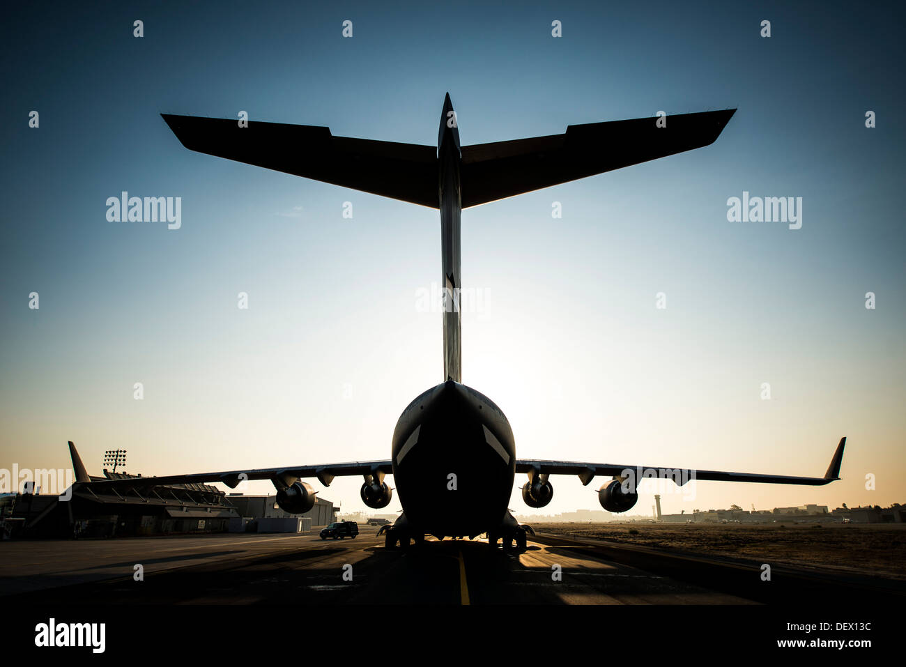 The sun rises above the final U.S. Air Force C-17 Globemaster III, P-223, as crew members arrive at the Boeing plant Sept. 12, 2 - Stock Image