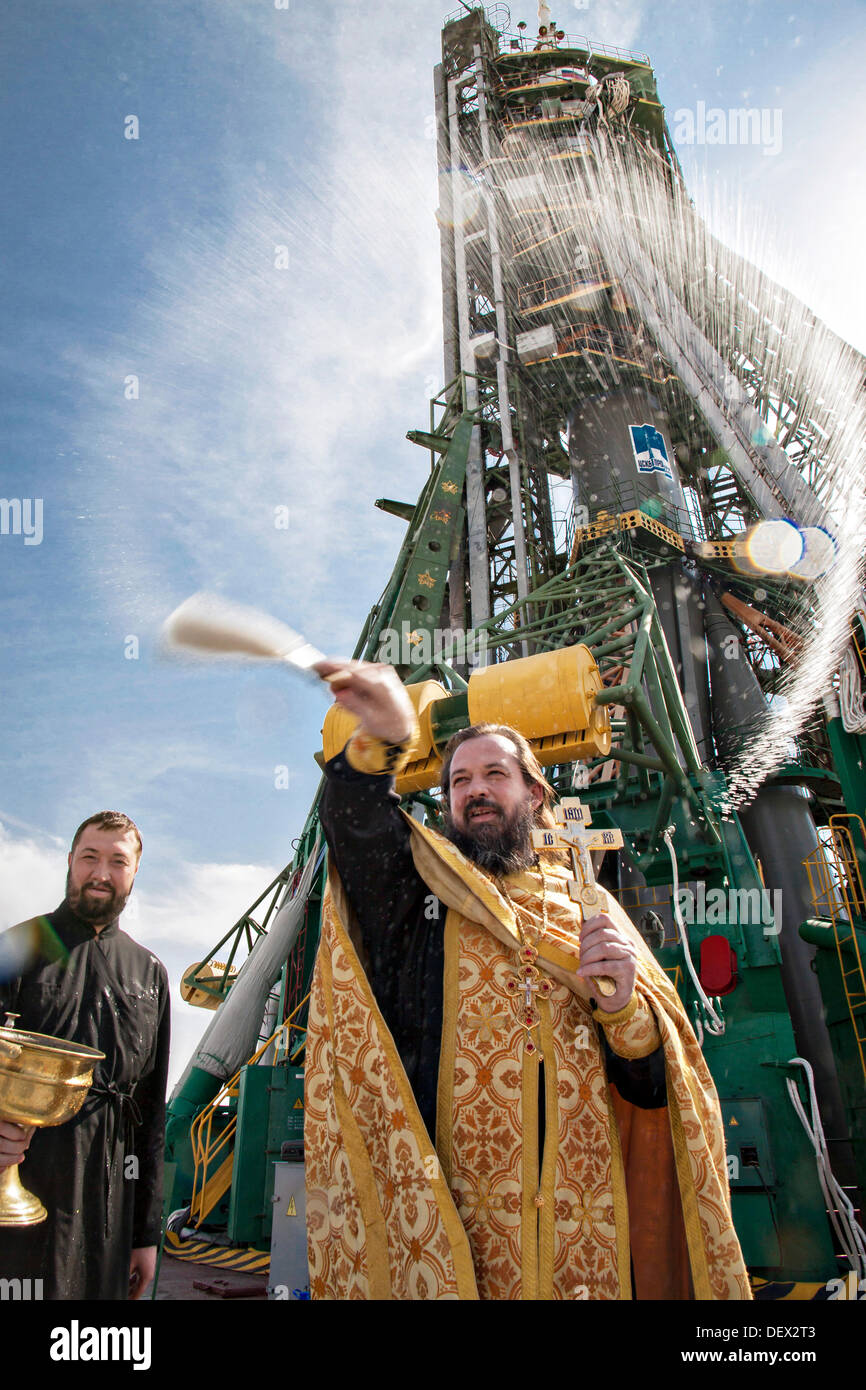 A Russian Orthodox priest blesses the Soyuz rocket on the launch pad at the Baikonur Cosmodrome September 24, 2013 Stock Photo