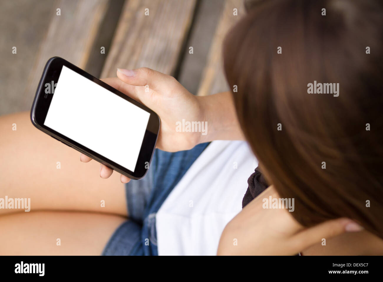 Young girl holding 5 inch touchscreen smartphone - Stock Image