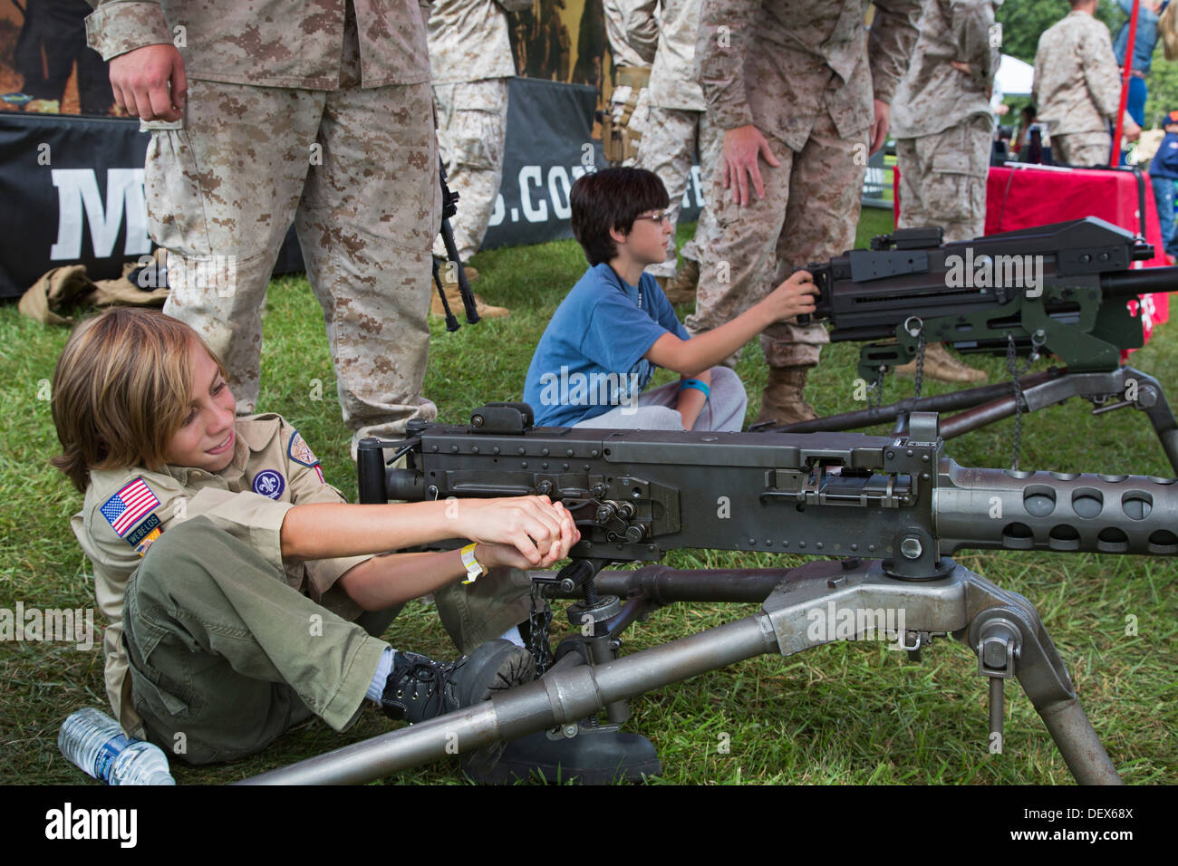 A Boy Scout handles a weapon at a Marine Corps booth during a weekend Scout gathering at a suburban Detroit park. - Stock Image