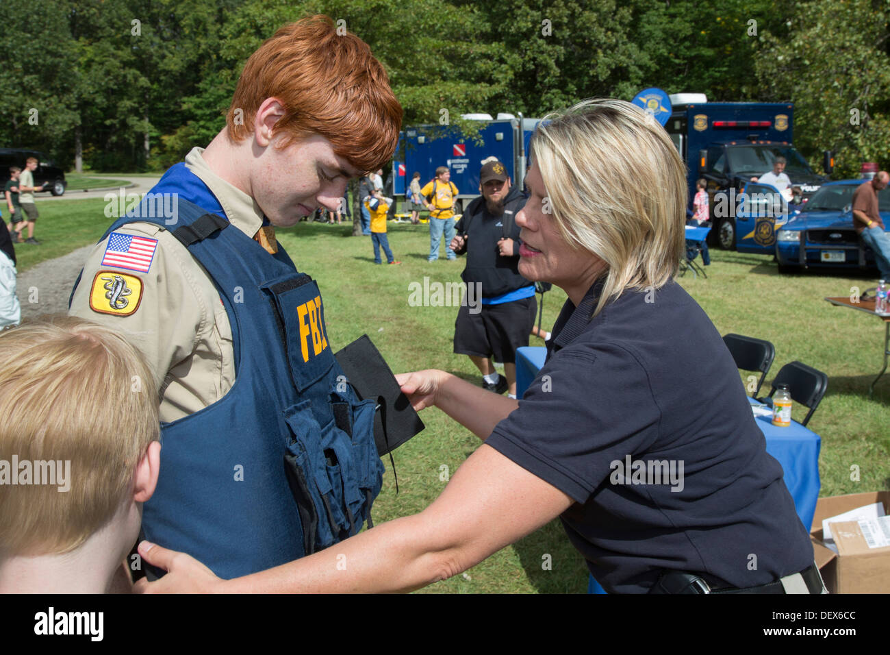 An FBI agent helps a Boy Scout try on a bulletproof vest during a Scout gathering at a suburban Detroit park. Stock Photo