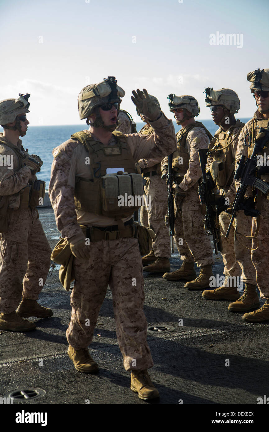 U.S. Marines assigned to Company L, Battalion landing Team 3/2, 26th Marine Expeditionary Unit (MEU), are briefed on target iterations during a live fire exercise on the flight deck of the USS San Antonio (LPD 17), at sea, Sept. 12, 2013. The 26th MEU is Stock Photo