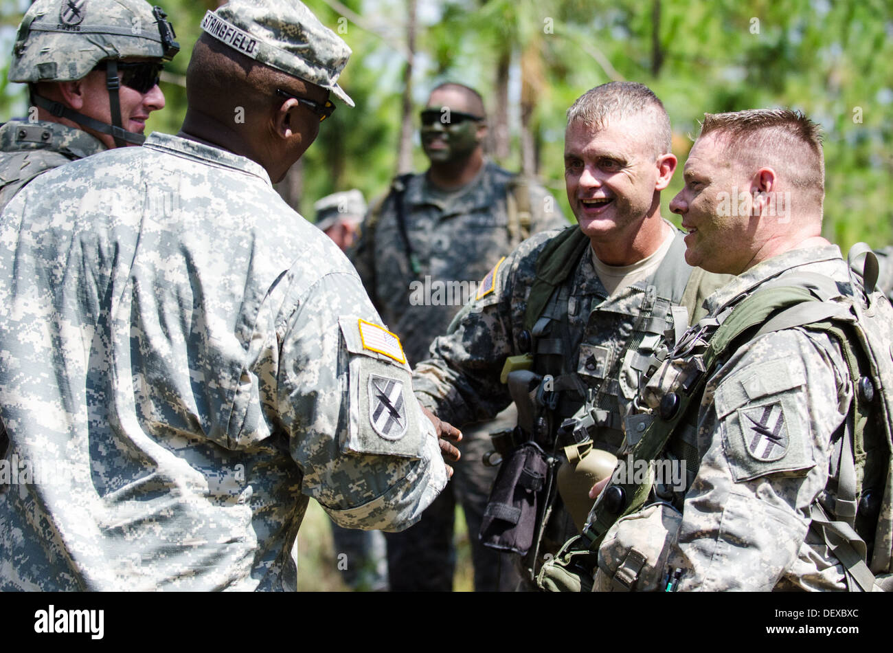 Georgia National Guard Command Sgt. Maj. Phillip Stringfield talks with HHC, 1-121 Infantry Soldiers after a platoon attack drill. - Stock Image