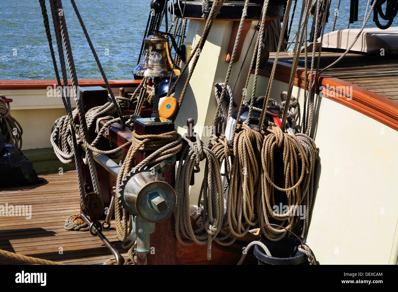 The Ropes, Rigging Pulleys And Bell At The Foot Of The Mainmast On An Antique Replica Sailing Vessel - Stock Image