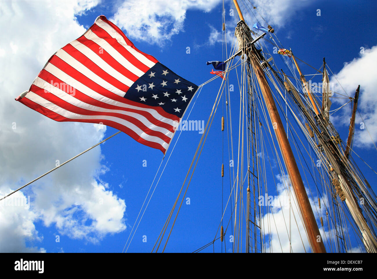 An American Flag, Mast And Rigging Against A Deep Blue Cloudy Sky During The Perry 200 Commemoration, Erie Pennsylvania, USA - Stock Image