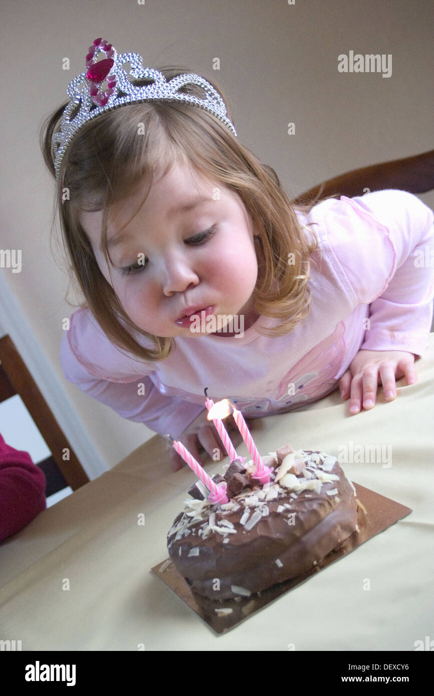 3 Year Old Girl Blowing A Candle Out On Her Birthday Cake