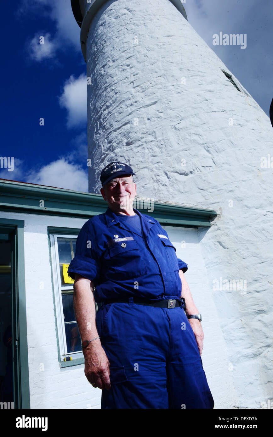 Coast Guard auxiliary member Rolland Weeman stands in front of the Portland Head Lighthouse as spectators take their turn climbing the tower in Cape Elizabeth, Maine, Sept. 14, 2013. 'This is a gorgeous place to volunteer my time. I got involved with the - Stock Image
