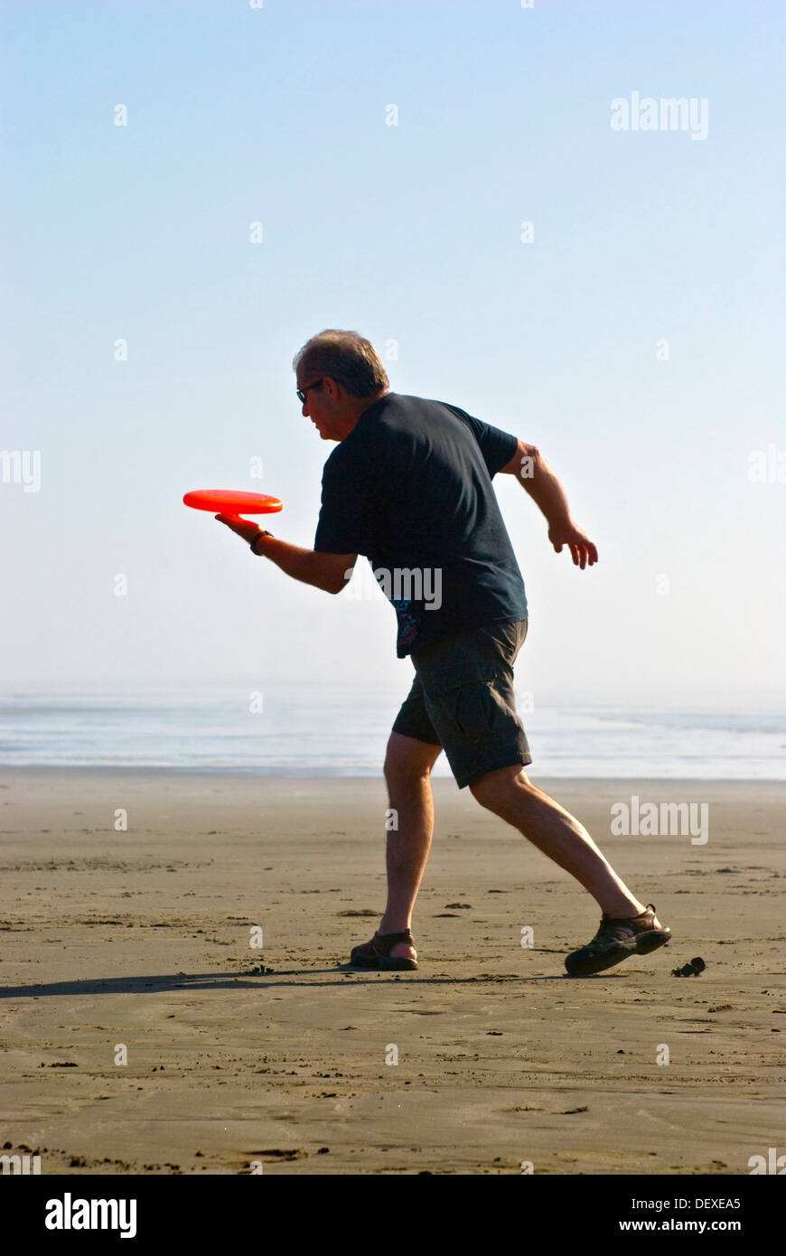 Man playing freestyle frisbee on California beach - Stock Image