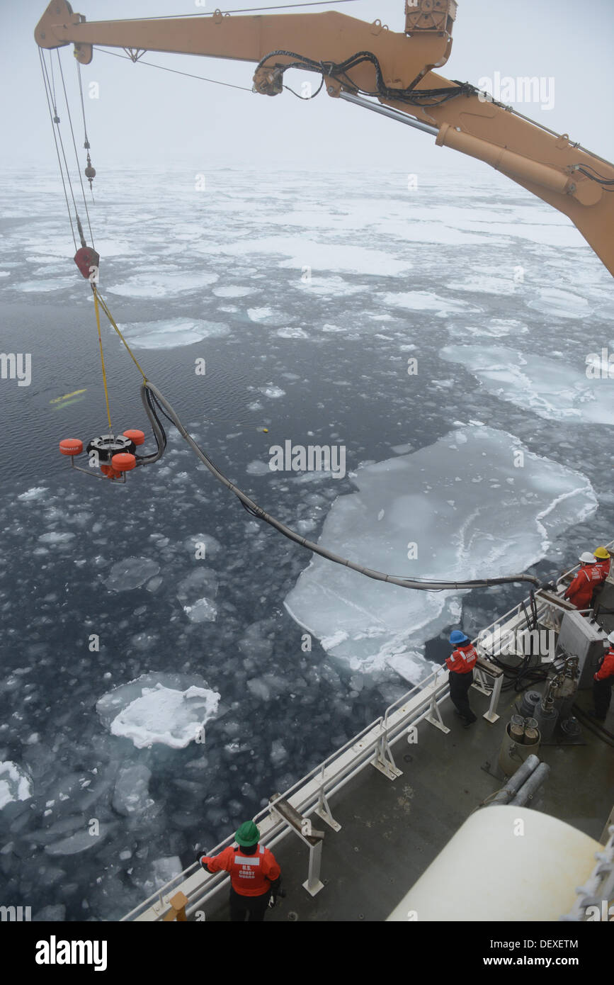 Members of the Coast Guard Cutter Healy deck department lower an oil skimmer into the ice-laden Beaufort Sea during a simulated - Stock Image