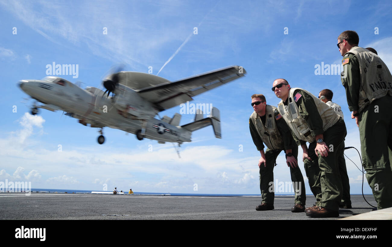 Landing signal officers observe an E-2C Hawkeye from the Liberty Bells of Airborne Early Warning Squadron (VAW) 115 as it lands - Stock Image