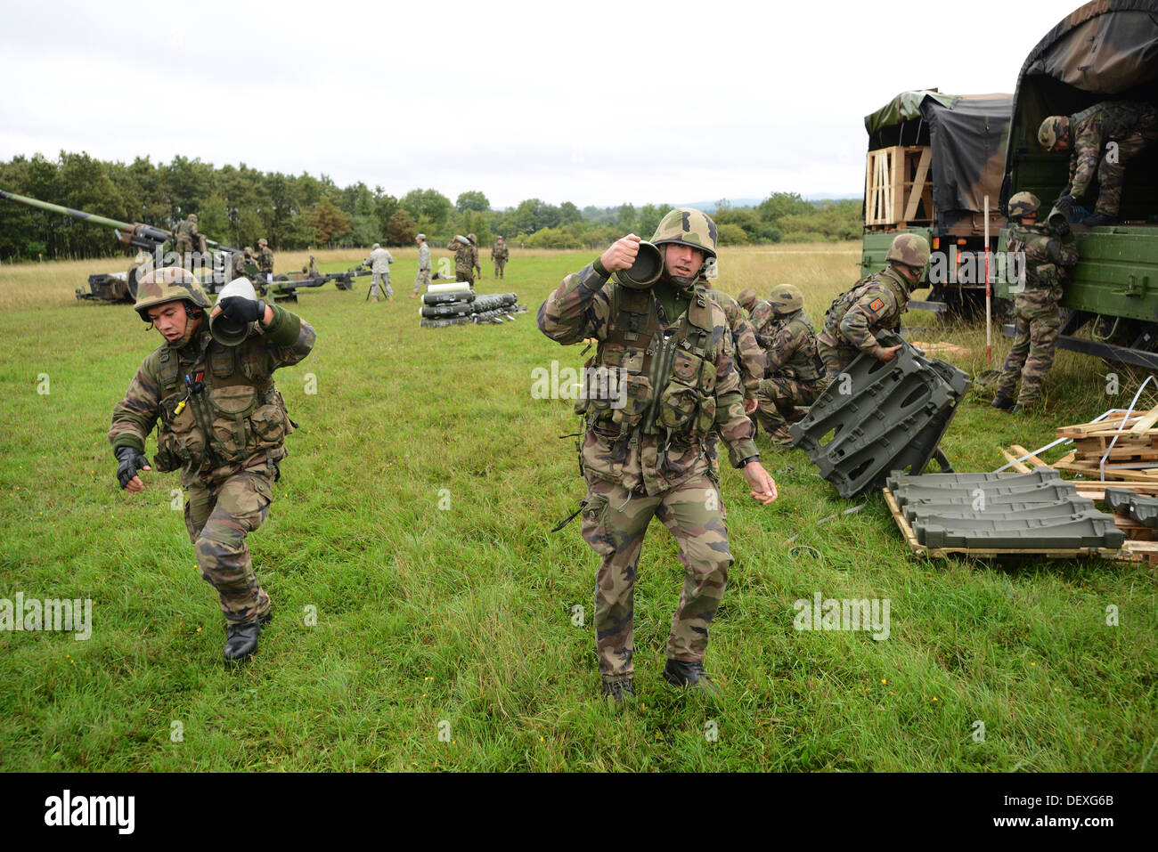 French soldiers carry 155 mm rounds to prepare for a live fire exercise during Combined Endeavor at the Joint Multinational Training Command's Grafenwoehr Training Area, Germany, Sept. 17, 2013. Combined Endeavor is an annual command, control, communicati - Stock Image