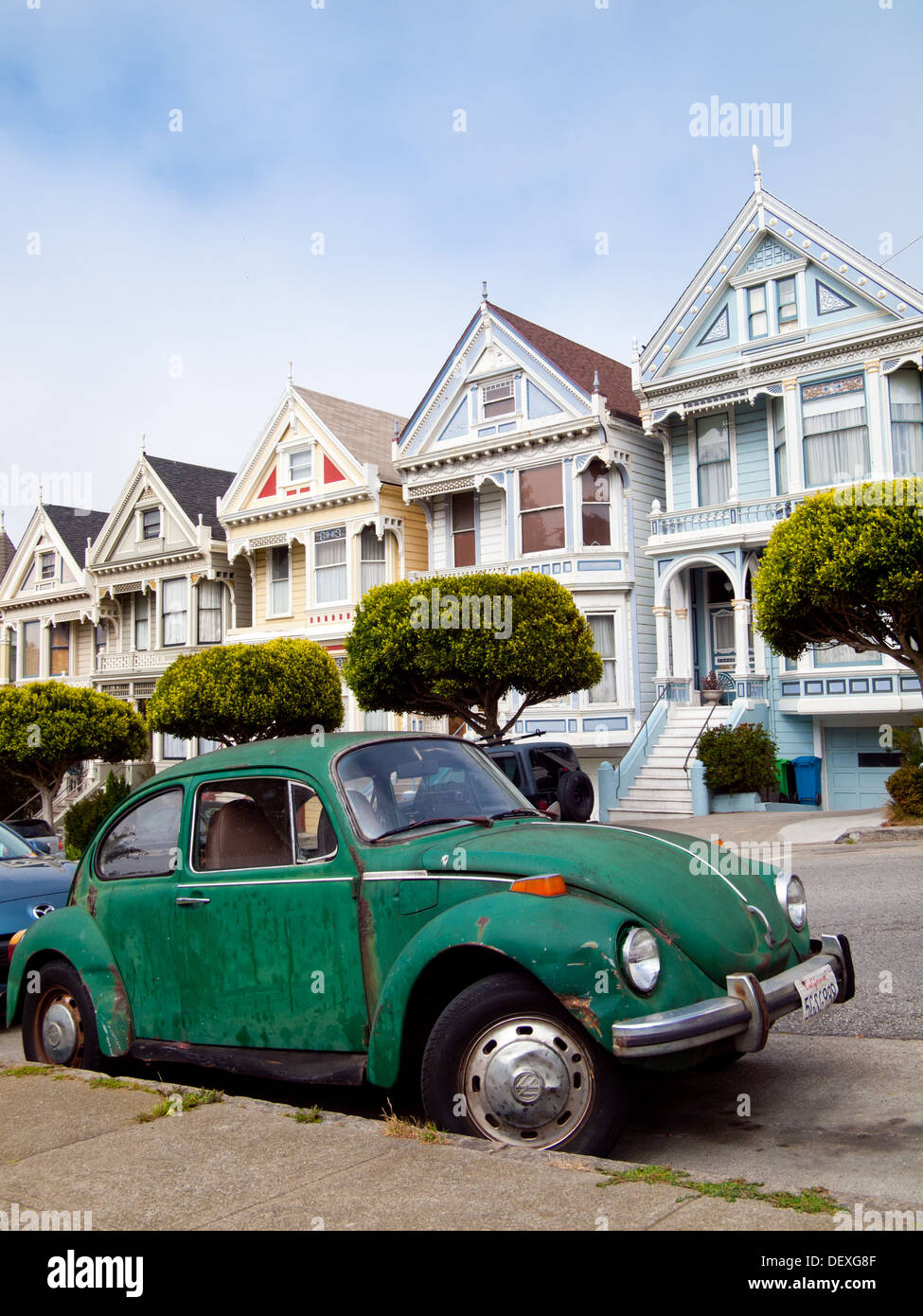 """A green Volkswagen Beetle parked in front of the """"Painted Ladies"""" row of Victorian Houses on Steiner Street (at Stock Photo"""