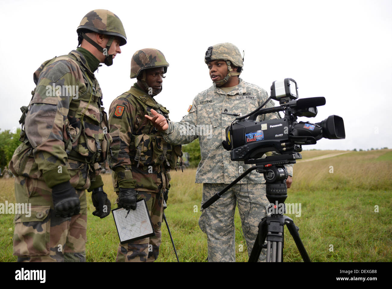 U.S. Army Staff Sgt. Stevens, AFN Bavaria, in a conversation with French Army soldiers during Combined Endeavor 2013 (CE13) at the Joint Multinational Training Command's Grafenwoehr Training Area, Germany Sept. 17. CE13 is a multinational command, control - Stock Image