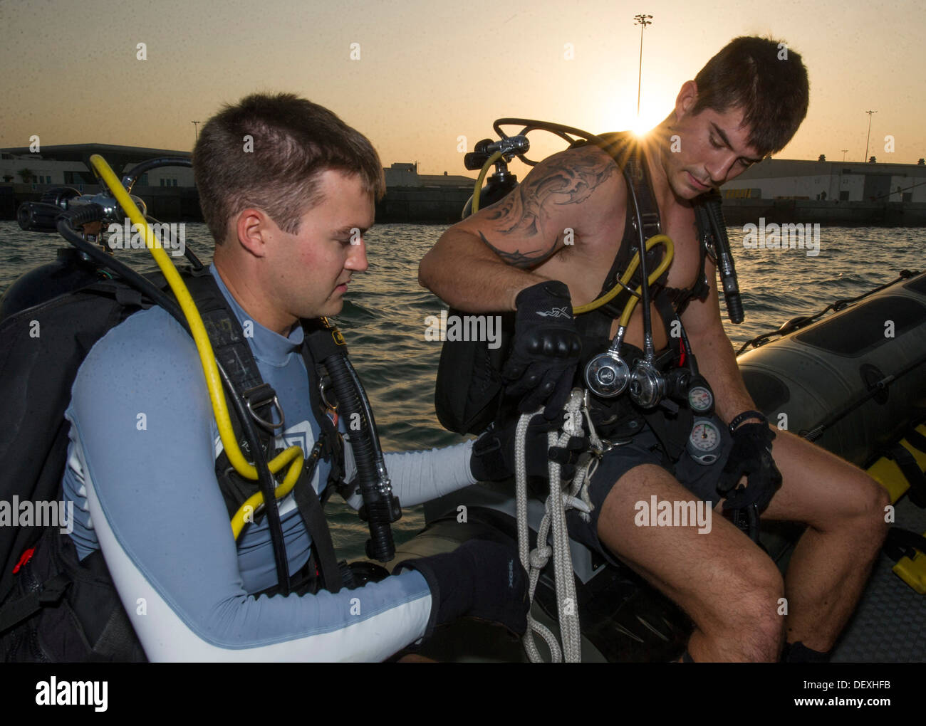 Navy Diver 2nd Class Trent Gobble and Mass Communication Specialist 3rd Class Wyatt Huggett, both assigned to Commander, Task Group (CTG) 56.1, prepare their gear for an early morning anti-terrorism force protection inspection dive. CTG 56.1 conducts mari - Stock Image