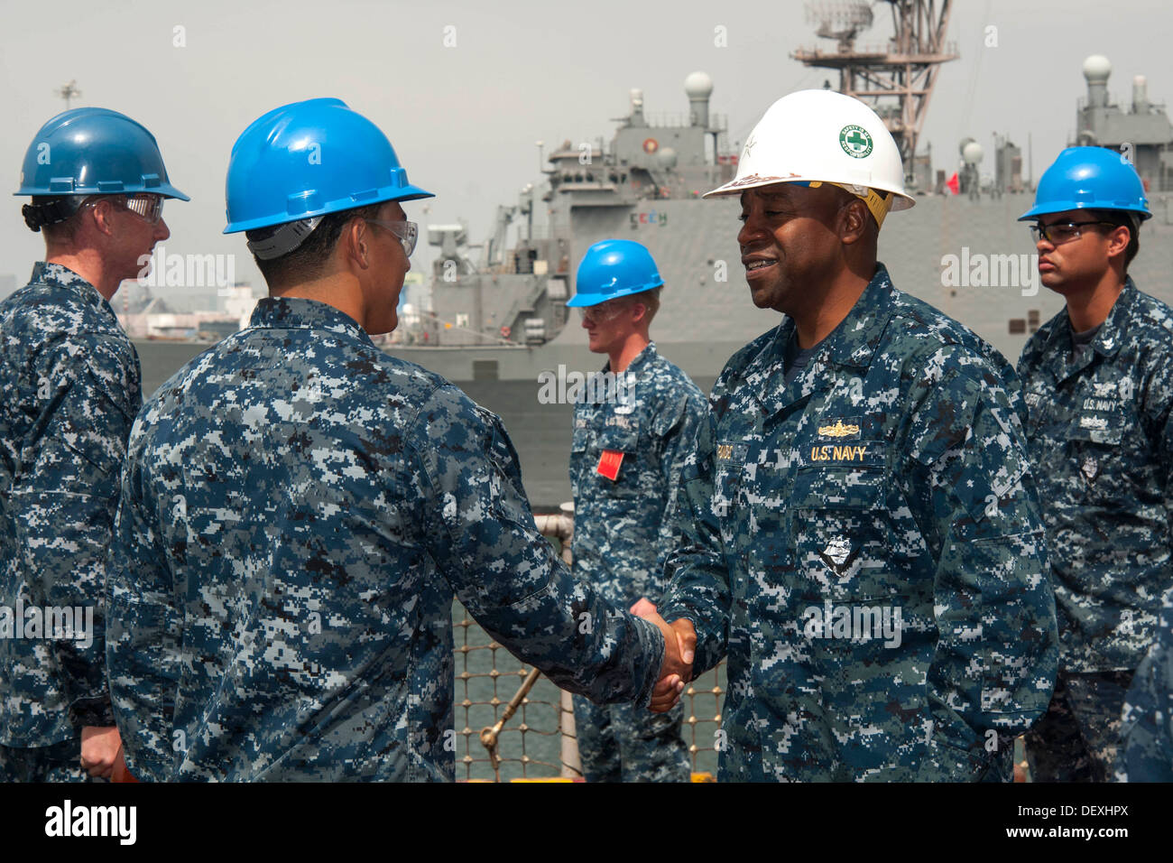 Commander, Expeditionary Strike Group 3 Rear Adm. Frank L. Ponds shakes hands with Sailors during his arrival to Stock Photo