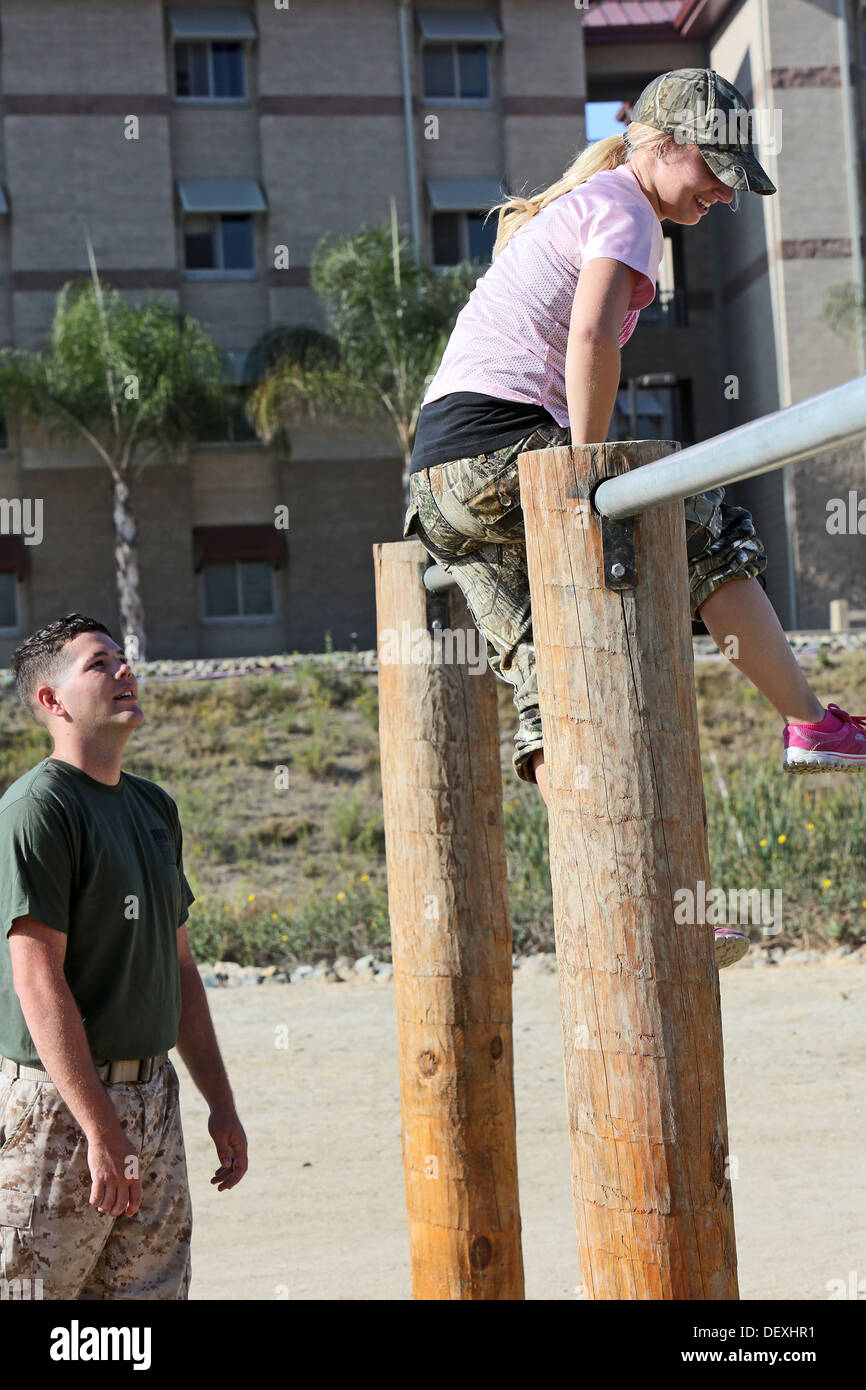 Corporal Steven Nixon, a combat engineer with 7th Engineer Support Battalion, 1st Marine Logistics Group, assists his wife, Alyssa, as she conducts the obstacle course during Jane Wayne Day, Sept. 13, 2013. The event gave spouses a chance to learn more ab - Stock Image