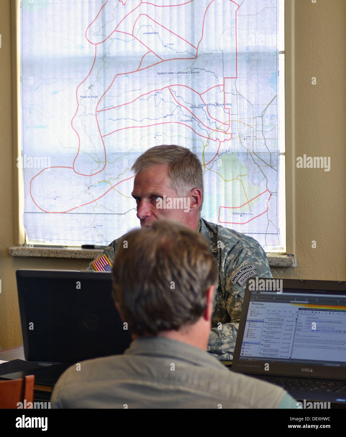 Lt. Col. Mitch Utterback, state inter-agency and liaison officer, Colorado National Guard, talks with supporting emergency agencies, at Boulder Municipal Airport in Boulder, Colo., Sept. 17, 2013. Colorado and Wyoming National Guard units were activated t - Stock Image