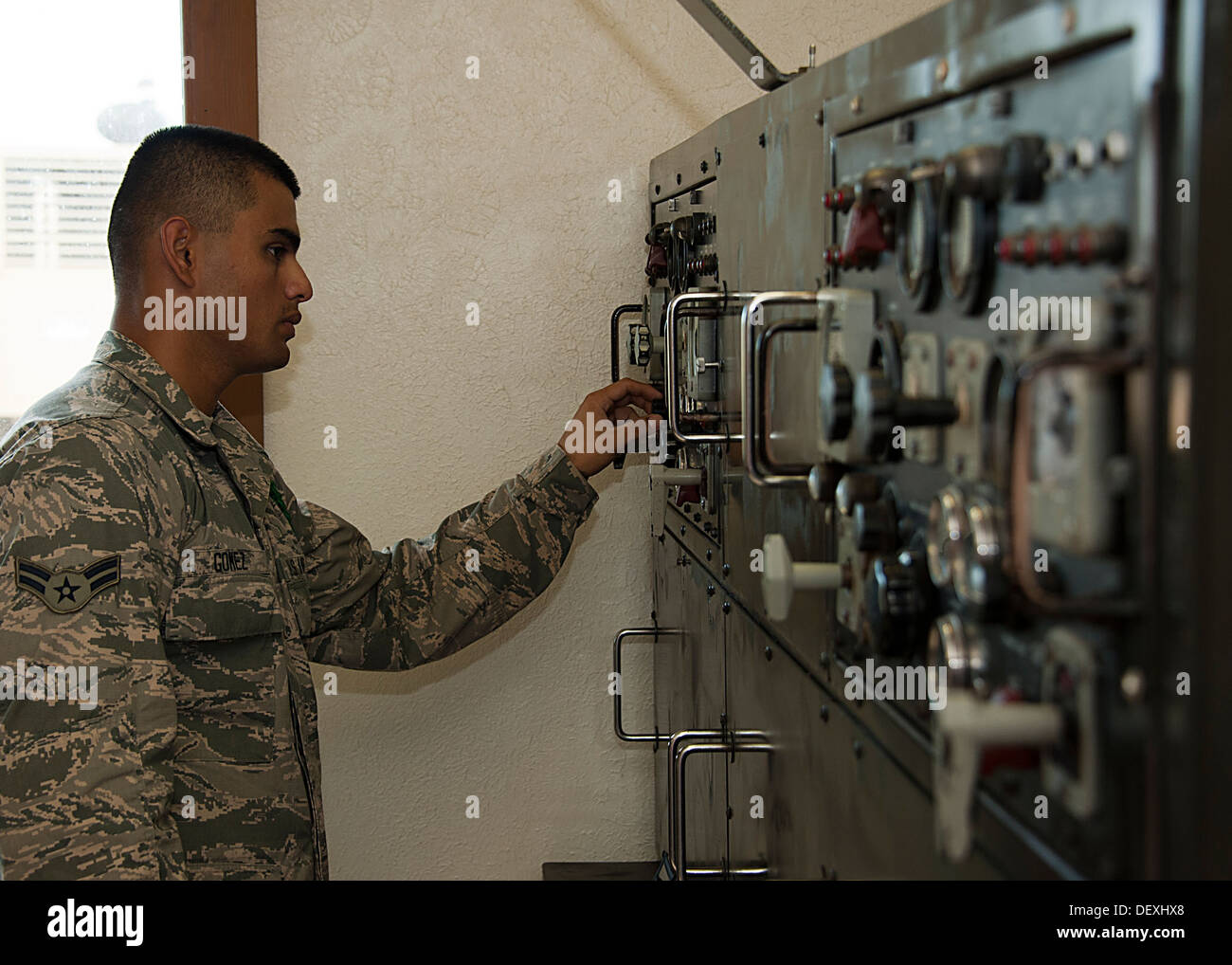Airmen 1st Class Hans Gomez, 366TH Civil Engineering Squadron student leader, balance the load equally between the running and incoming generators on an equipment rack with generator control panels, Sept. 18, 2013. Students learn and adjust the voltage as - Stock Image